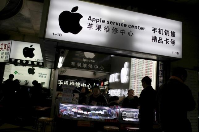 Customers and salespersons are seen at an Apple maintenance service store at a mobile phone market in Shanghai, in this January 24, 2013 file photo.