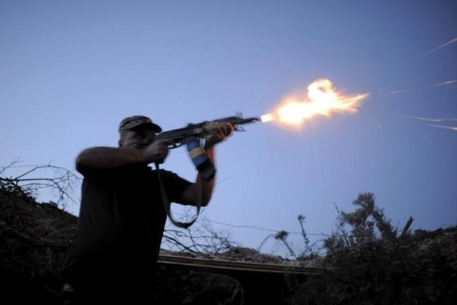 A serviceman of the Ukrainian armed forces fires a weapon in the direction of positions of units of the armed forces of the self-proclaimed Donetsk People's Republic during a battle in Avdiivka, Donetsk region, Ukraine, August 23, 2015.