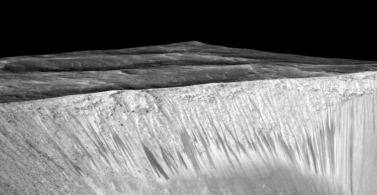 "Dark, narrow streaks called ""recurring slope lineae"" line the walls of Garni crater on Mars. The dark streaks are up to a few hundred meters in length. Researchers believe they may provide evidence of flowing, briny water on the Red Planet. NASA/JPL/University of Arizona"