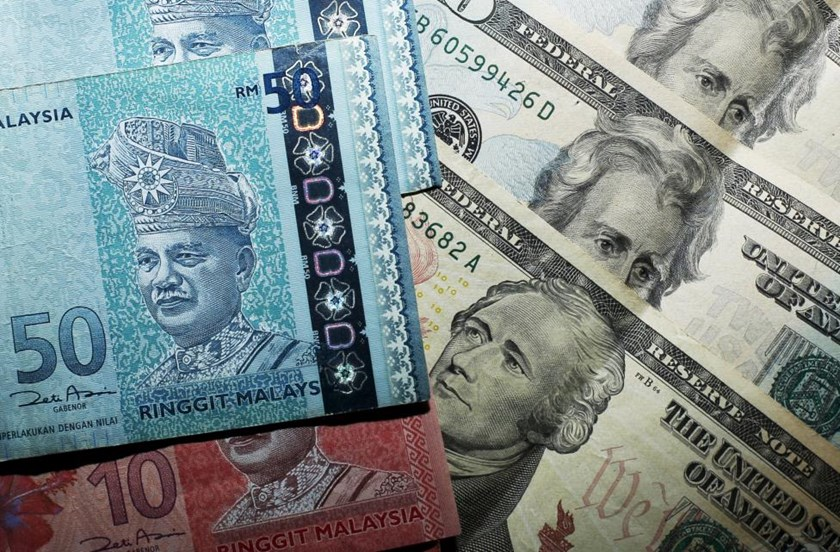 Malaysian ringgit notes are seen among U.S. dollar bills in this photo illustration taken in Singapore in this August 24, 2015 file photo.