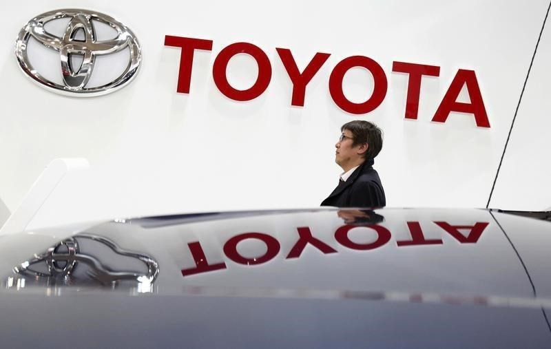 A visitor walks under a logo of Toyota Motor Corp at the company's showroom in Tokyo February 4, 2015.