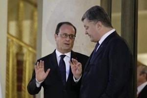 French President Francois Hollande (L) reacts as he speaks with Ukraine's President Petro Poroshenko after a summit on the crisis in Ukraine at the Elysee Palace in Paris, France, October 2, 2015.