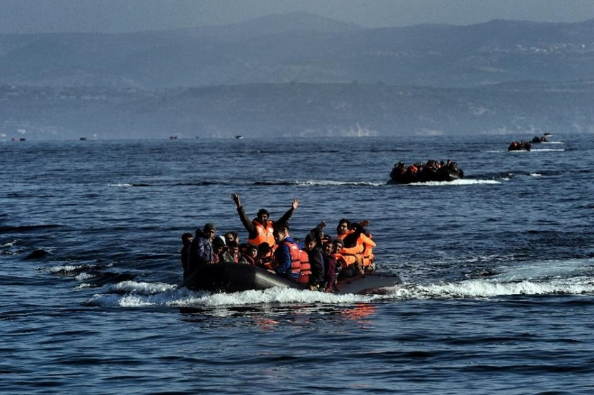 Migrants aboard dinghies reach the Greek island of Lesbos after crossing the Aegean sea from Turkey on October 4, 2015