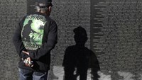 A U.S. military combat veteran stares at a name on the wall of the National Vietnam Veterans Memorial on Veteran's Day in Washington, November 11, 2014.