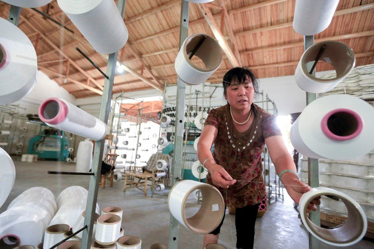 An employee works in a factory producing textiles in Shaoxing, Zhejiang Province, China
