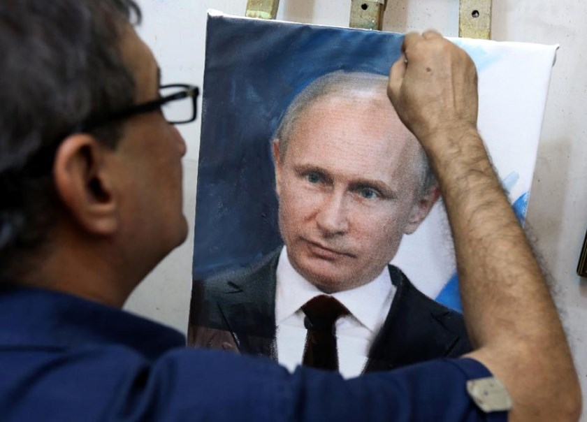 Iraqi artist Mohammed Karim Nihaya touches up a painting of Russian President Vladimir Putin in his studio in the Karada district of Baghdad on October 7, 2015