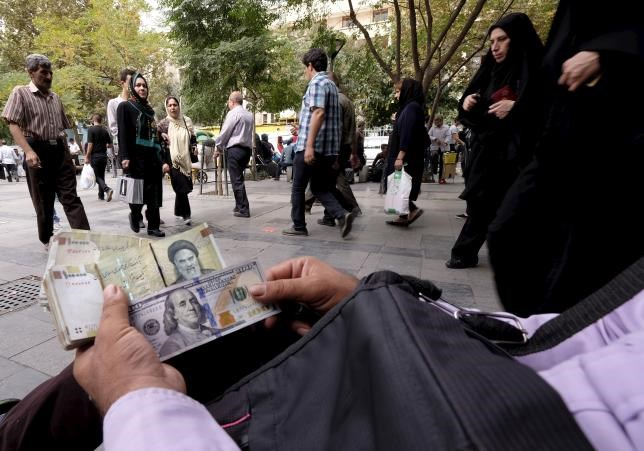A money changer displays U.S. and Iranian banknotes at the Grand Bazaar in central Tehran October 7, 2015.