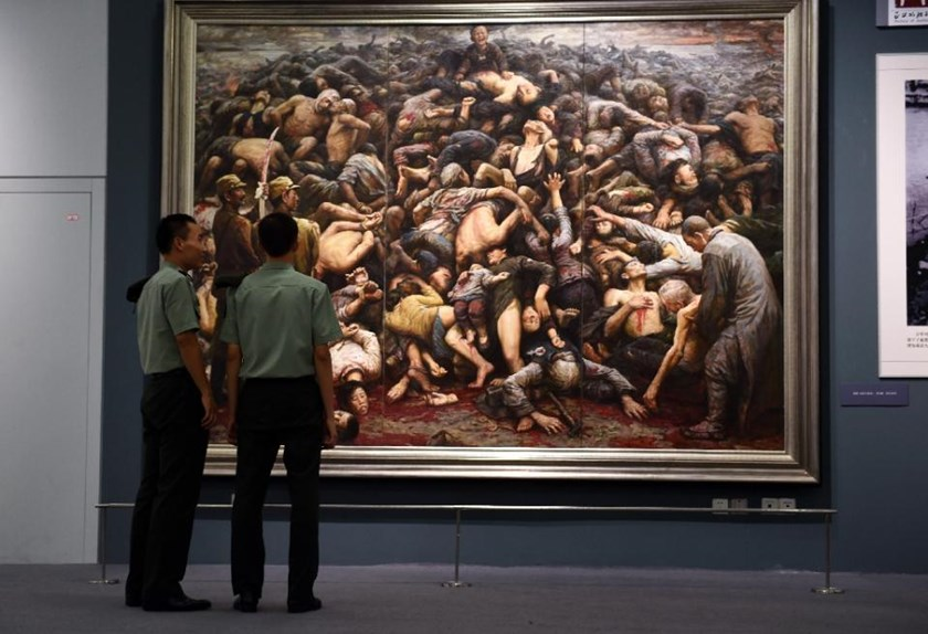 File picture shows Chinese soldiers looking at a painting depicting the Nanjing massacre, at an exhibition about World War II in Beijing