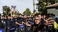 A woman reacts near a row of police officers blocking the way to the site of the twin bombings during a rally to remember the victims in Ankara on October 11, 2015
