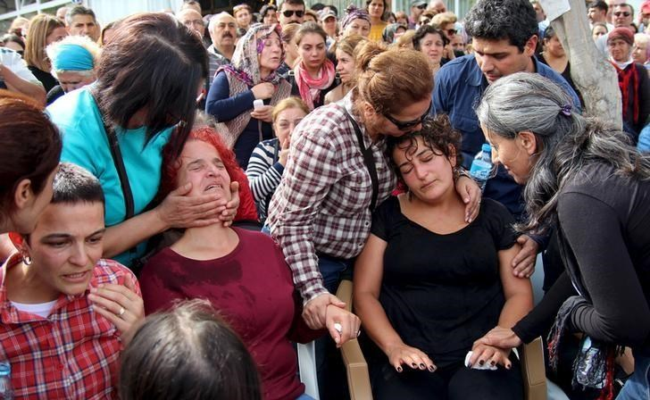 Family members of Korkmaz Tedik, a victim of Saturday's bomb blasts, mourn over his coffin during a funeral ceremony in Ankara, Turkey, October 11, 2015.