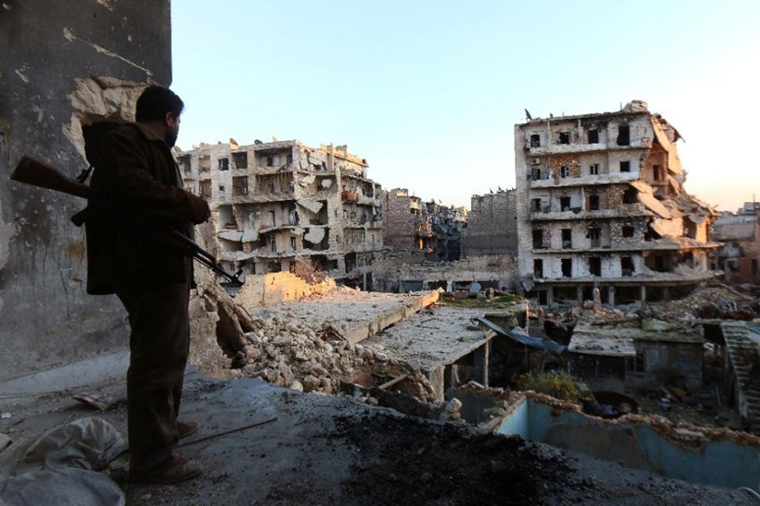 A rebel fighter stands in a building overlooking the damage from fighting in the city of Aleppo on December 16, 2013
