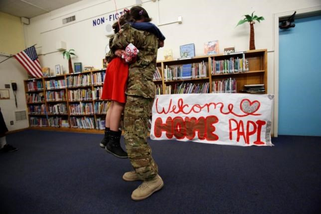 California Army National Guard helicopter pilot David Duran hugs his daughter Luz after surprising her on Valentine's Day at Gates Elementary School in Los Angeles, California February 14, 2014. Duran had just returned from a year's deployment in Afghanistan.
