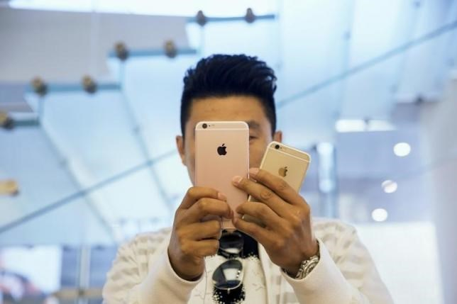 A man takes pictures as Apple iPhone 6s and 6s Plus go on sale at an Apple Store in Beijing, China September 25, 2015.