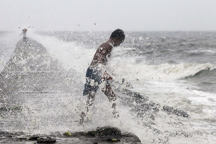A boy searches for reusable plastic bottles while being pelted by waves brought by typhoon Koppu in Manila Bay October 18, 2015.