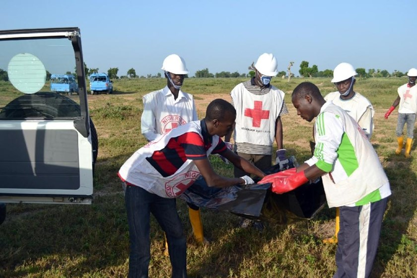Red Cross officials remove a body at the scene of a blast in Miduguri, Nigeria on October 16, 2015, blamed on Boko Haram
