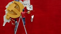 Workers peel papers off a wall as they re-paint the Chinese Communist Party flag on it at the Nanhu revolution memorial museum in Jiaxing, Zhejiang in a May 2015 file photo. Photo: Reuters
