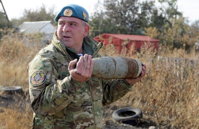 Pro-Russian rebel sapper Konstantin, 42, carries an unexploded shell in Veseloe village, near Donetsk on October 18, 2015