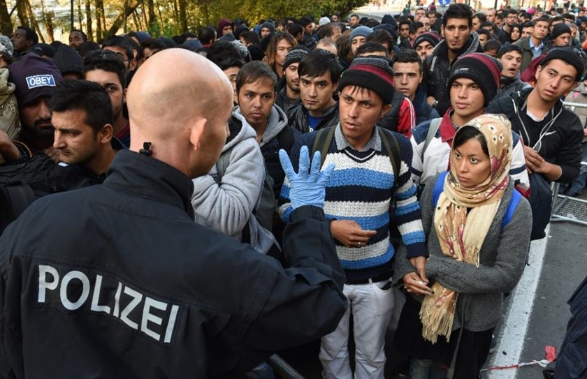 A German police officer speaks with migrants waiting to cross the Austrian-German border near the Bavarian town of Passau, southern Germany, on October 28, 2015