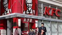 A man holds instant noodle packs in front of a KFC restaurant in Beijing, in this October 23, 2013 file picture.