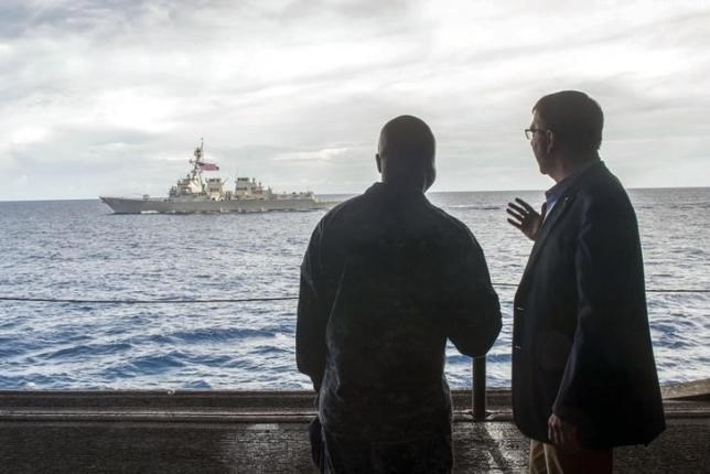 U.S. Secretary of Defense Ash Carter (R) speaks with U.S. Navy Cmdr. Robert C. Francis Jr., as Carter and Malaysian Defense Minister Hishammuddin Hussein (Not Pictured) visited the USS Theodore Roosevelt aircraft carrier in the South China Sea