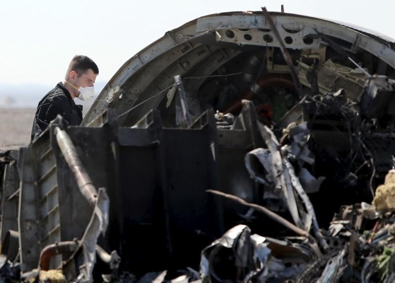 A military investigator from Russia stands near the debris of a Russian airliner at its crash site at the Hassana area in Arish city, north Egypt, November 1, 2015.
