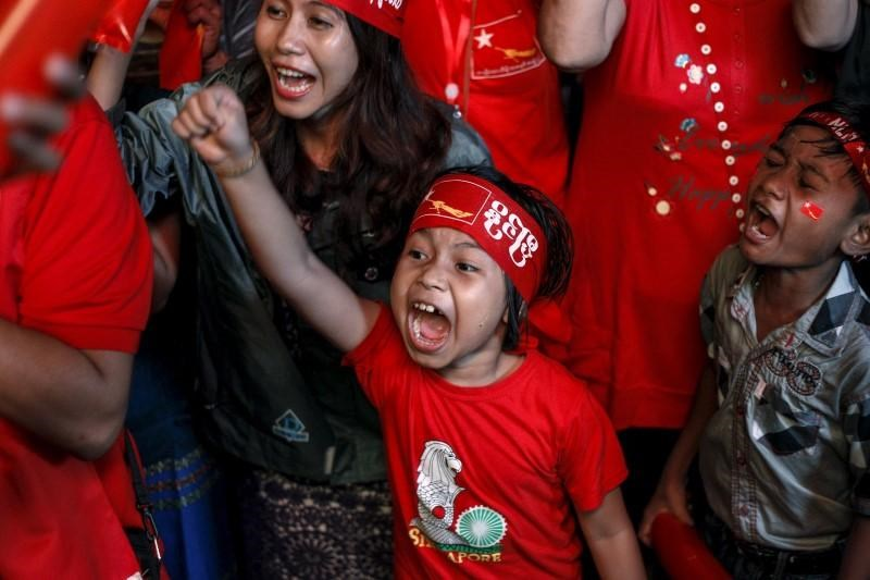 Supporters celebrate as they watch official results from the Union Election Commission on an LED screen in front of the National League for Democracy Party (NLD) head office in Yangon, November 9, 2015.