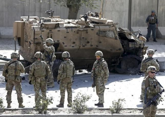 NATO soldiers stand near a damaged NATO military vehicle at the site of a suicide car bomb blast in Kabul, Afghanistan, October 11, 2015.