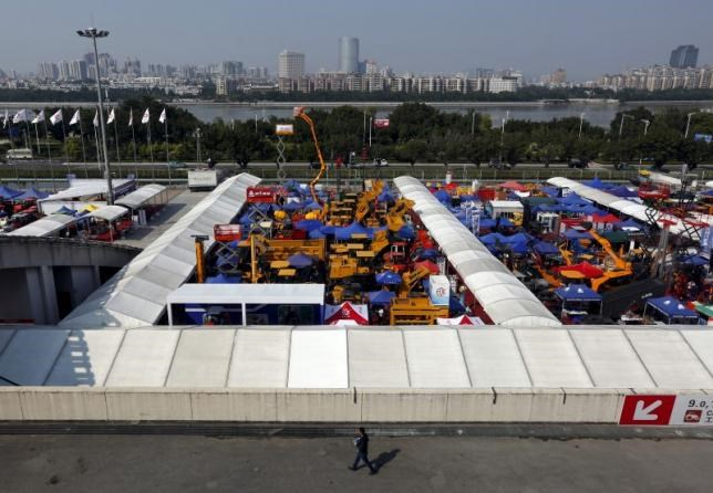 A man walks past construction vehicles on display during the China Import and Export Fair, also known as Canton Fair, in the southern Chinese city of Guangzhou October 15, 2015.