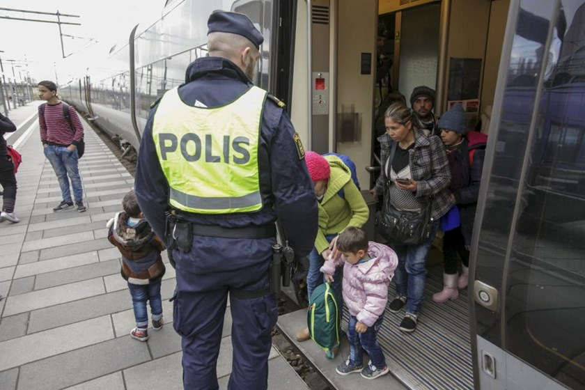 Police gather a group of migrants coming off an incoming train at the Swedish end of the bridge between Sweden and Denmark, in Hyllie district, Malmo November 12, 2015