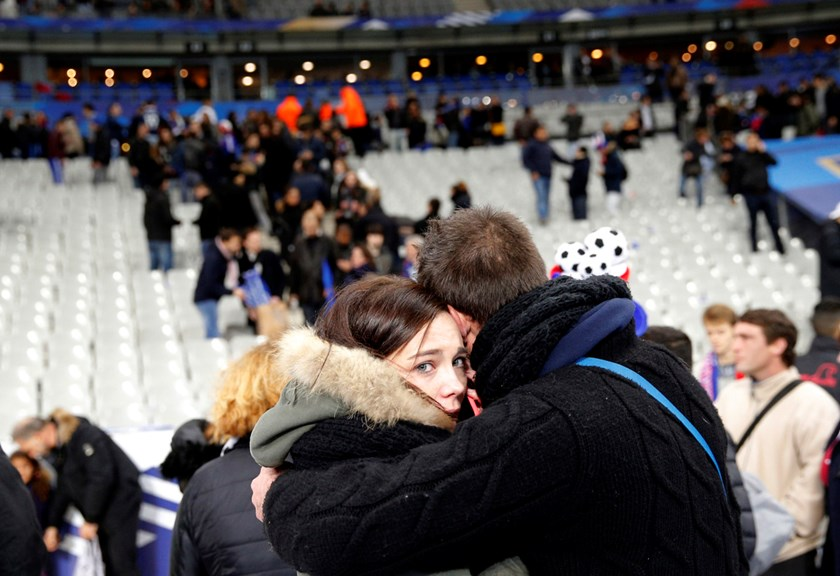 A supporter conforts a friend after invading the pitch of the Stade de France stadium at the end of the international friendly soccer match between France and Germany in Paris, on Friday, Nov. 13.