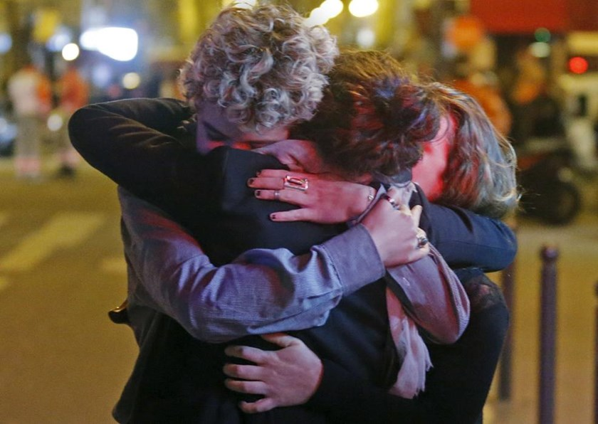 People hug on the street near the Bataclan concert hall following fatal attacks in Paris, France, Nov. 14, 2015.