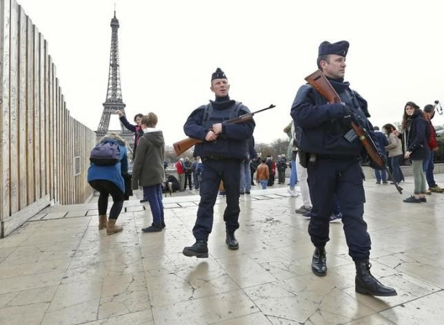 Police patrol near the Eiffel Tower the day after a series of deadly attacks in Paris , November 14, 2015.