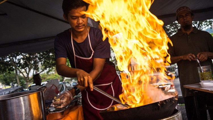 A chef cooks fried noodles at a food stall in a market in Johor Bahru, Johor, Malaysia.