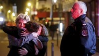People hug on the street near the Bataclan concert hall following fatal attacks in Paris.