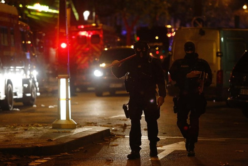 Members of a police intervention unit walk near the Bataclan concert hall in central Paris, on November 14, 2015