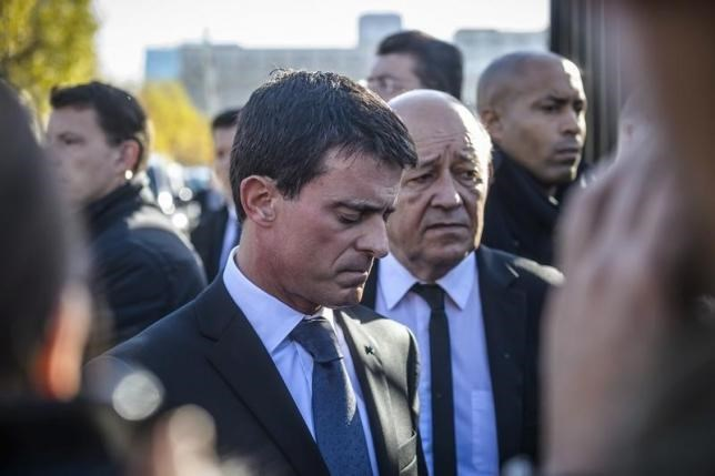 French Prime Minister Manuel Valls (L) and French Defense Minister Jean-Yves Le Drian react as they speak to journalists after they visited the psychological help center at the Ecole Militaire to assist survivors and the families of victims in Paris, France, November 15, 2015, two days after a series of fatal shootings in the French capital.