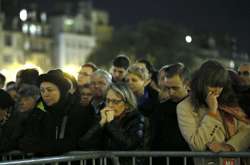 People gather outside Notre Dame Cathedral where a mass is held following a series of deadly attacks in Paris, November 15, 2015.