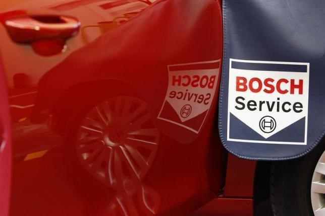 A Bosch Service sign is reflected in a car door while a product expert for diagnostics equipment of German auto parts supplier Robert Bosch analyses a car in a workout garage in Plochingen near Stuttgart April 15, 2013.