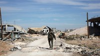 A Syrian pro-government fighter inspects bombing damage in Arbid in the northern province of Aleppo, on November 12, 2015