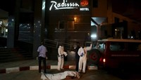 Malian officials prepare to lift a corpse into an emergency vehicle outside the Radisson hotel in Bamako, Mali, November 20, 2015.