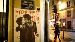 A drawing which reproduces French photographer Robert Doisneau's picture ''Le baiser de l'Hotel de ville'' (Kiss by the Town Hall) with the words ''Not even hurt'' over it, is seen on a wall near the Bataclan concert hall in Paris, November 20, 2015.