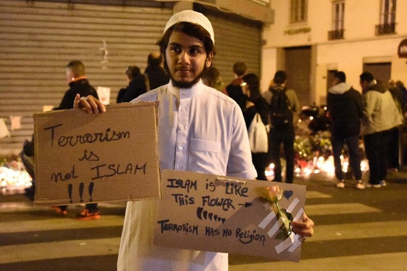"A Muslim holds a placard reading ""Terrorism is not Islam. Islam is like this flower. Terrorsim has no religion"" during a gathering on November 15, 2015 at ""Le Carillon"" restaurant, one of the sites attacked in Paris."