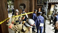 Police officers and fire fighters investigate at the south gate of Japan's controversial Yasukuni Shrine where there was an explosion and burned the ceiling and wall of the public bathroom, in Tokyo, Japan, in this photo taken by Kyodo November 23, 2015.