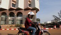 A man drives a motorcycle past the Radisson Blu hotel in Bamako, Mali, November 22, 2015.