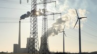 Wind turbines and electricity pylons flank a coal-fired power plant in Germany. Photographer: Sean Gallup/Getty Images
