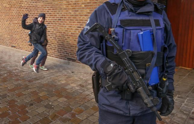 A Belgian police officer stands guard outside a school in central Brussels November 25, 2015.