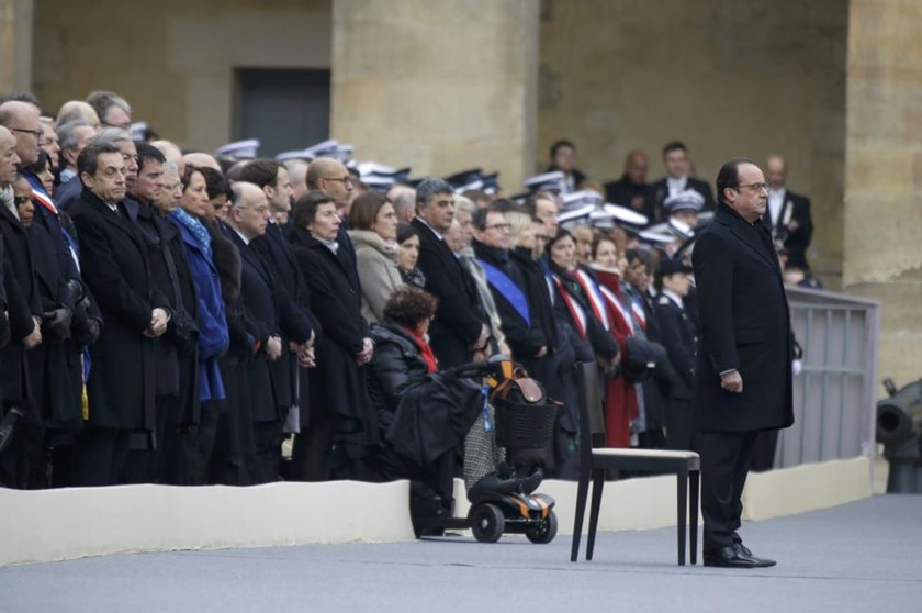French President Francois Hollande (R) stands in front of members of the French government, officials and guests during a ceremony to pay a national homage to the victims of the Paris attacks at Les Invalides monument in Paris, France, November 27, 2015.