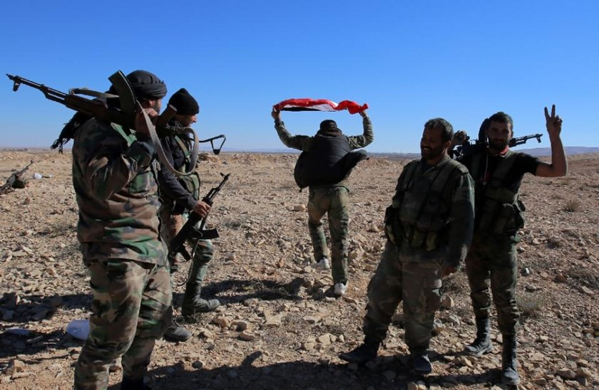 Syrian pro-regime forces celebrate after capturing territory from the Islamic State group near Mahin in Homs province, on November 14, 2015