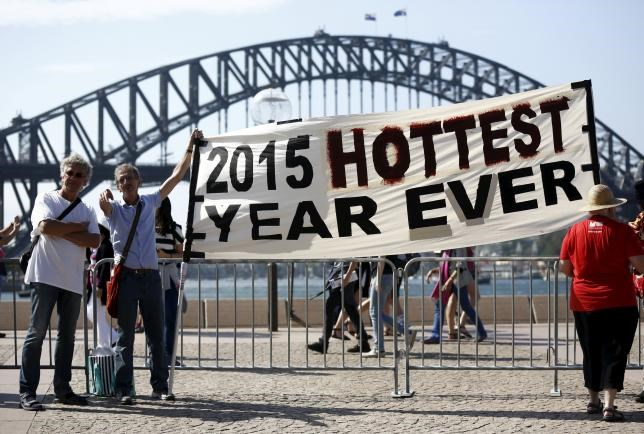 Protesters hold a banner in front of the Sydney Harbour Bridge during a rally ahead of the 2015 Paris Climate Change Conference, known as the COP21 summit, in Sydney's central business district, Australia November 29, 2015.