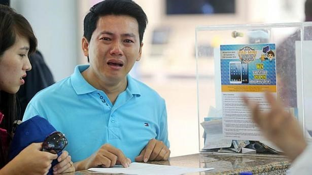 Pham Van Thoai, the Vietnamese tourist, cried as he begged a Mobile Air shop employees to give him his money back on Monday. Photo credit: LIANHE ZAOBAO